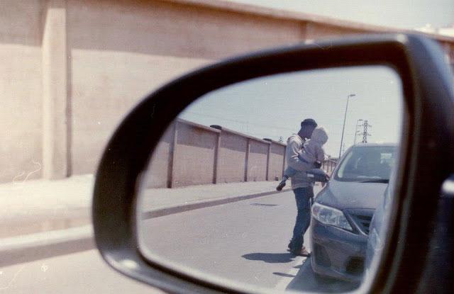 Un hombre pidiendo con un menor en brazos en una calle de Marruecos