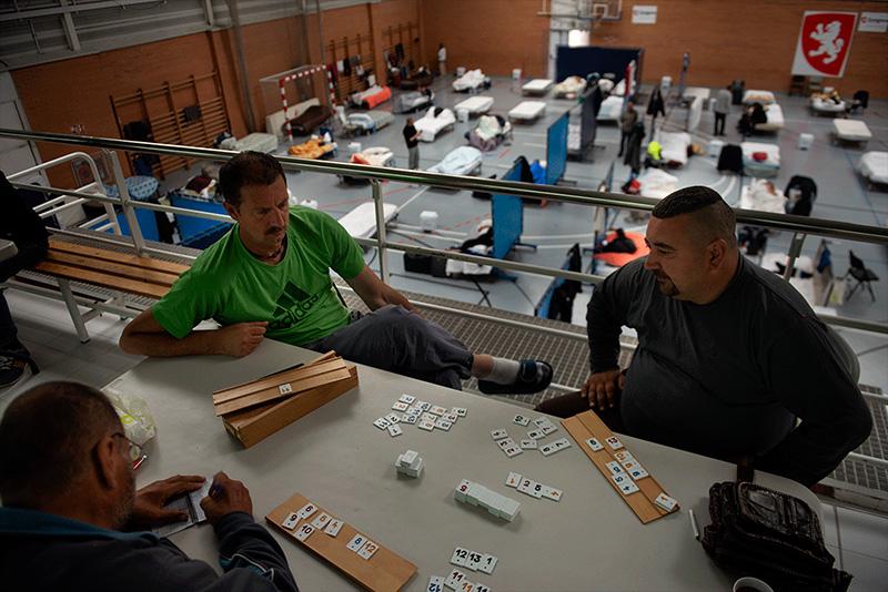 Judith Prat, sin título, 2020. Florin, Christian y Jon juegan al rummikub mientras permanecen confinados en el Pabellón deportivo Tenerías, habilitado en Zaragoza para acoger a las personas sin hogar
